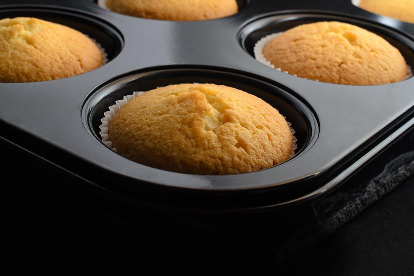 baked cupcakes in black muffin tin cooling on a slate