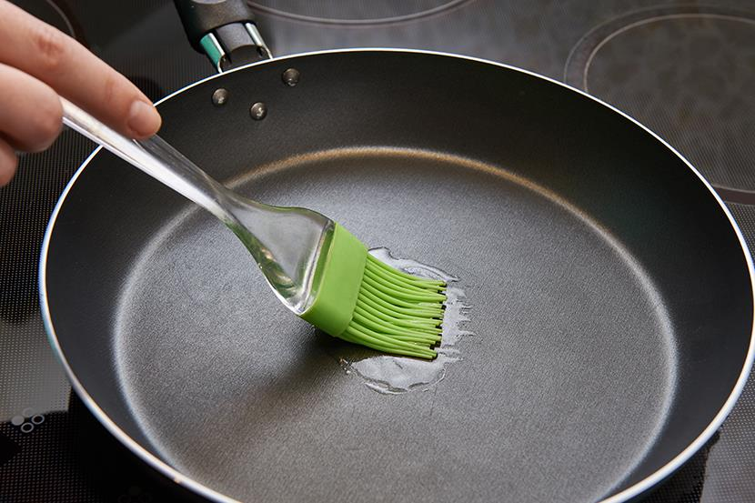 person using a basting brush to brush oil into a frying pan