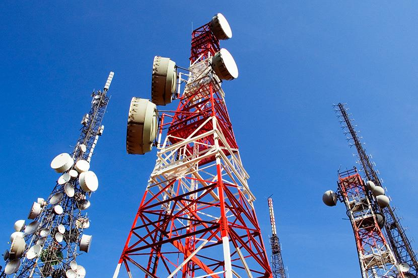 three telecommunications towers highlighted against a blue sky