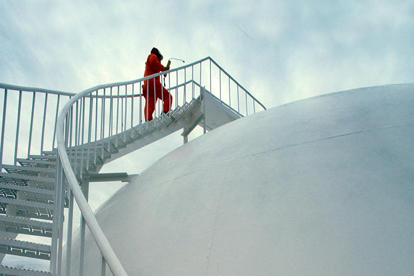 worker climbing steps to top of liquid gas storage tank at natural gas plants
