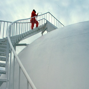worker climbing steps to top of liquid gas storage tank at natural gas plant