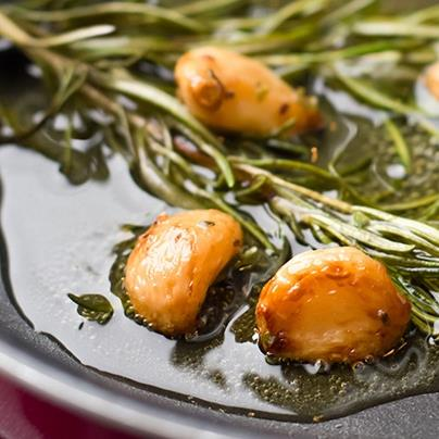 garlic cloves and rosemary sauteing in oilve oil in a frying pan
