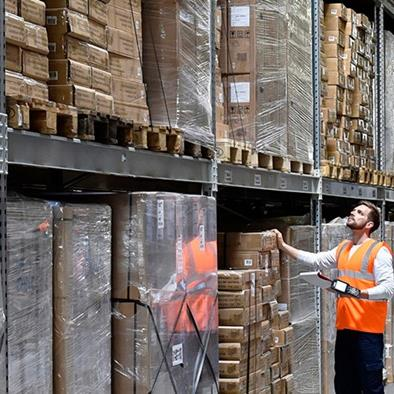 man in warehouse wearing orange safety vest looking up