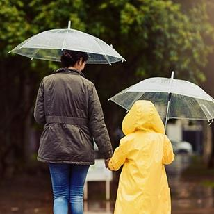 mother and child wearing raincoat are holding hands umbrellas walking through the rain