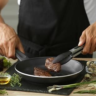 person cooking meat in nonstick skillet herbs on counter