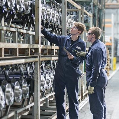 two men looking at rows of stored car axles on a shelving unit at a car plant