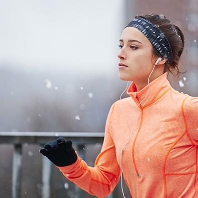 woman wearing jacket gloves hat jogging in winter weather