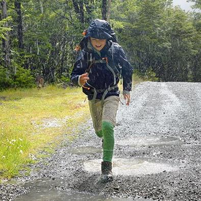 young boy wearing blue jacket running through the rain and smiling