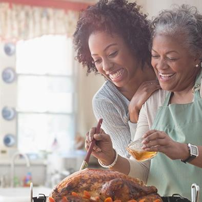 younger woman hugging older woman whos basting a turkey